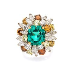 A Platinum, 18 Karat Yellow Gold, Emerald, Colored Diamond and Diamond Ring, Oscar Heyman Brothers, in a domed cluster design, containing one octagonal step cut emerald weighing approximately 8.83 carats, three round brilliant cut diamonds weighing approximately 0.86 carat total, 16 marquise cut diamonds weighing approximately 4.44 carats total, and 12 round brilliant cut orange and yellow diamonds (origin of color not tested) weighing approximately 4.24 carats total. - See more at: http://cata