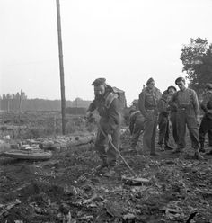 Sapper W.H. Lindstrom, 2nd Field Company, Royal Canadian Engineers (R.C.E.), sweeping for mines at a roadblock, Kappellen, Belgium,5 October 1944.