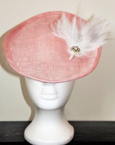 This is a pretty handmade oval fascinator on a pale pink sinamay base. It is decorated with a white and grey feather, with beautiful hand stitched grey pearls and swarovski crystal detailing. Elastic is stitched to the fascinator to enable you to attach it to your head. Other sinamay colours are available. There is currently 1 item in stock in pale pink, which can be shipped in 1 - 2 business days. However, if you require any other colour, please allow 1 - 2 weeks for me to make this.  The…