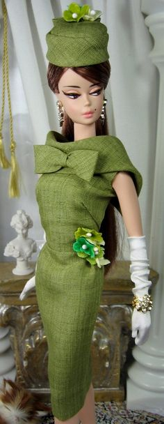 This iconic style sheath dress for Silkstone Barbie is cut from moss pure linen from India, fully lined in china silk, and features a portrait collar with dressmakers bow detail, vintage style milliners forget me nots at the waistline and button over snap back closure. The matching pillbox hat is fully lined and finished with a dressmakers bow and matching forget me nots. SHOES, SUNGLASSES, PURSE, GLOVES, DOLL AND DIORAMA NOT INCLUDED. Accessories are from Mattel Barbie Fashion Model Col...