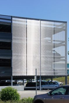 Architectural wire mesh as facade cladding at the car park Stauferklinikum. The resulting building envelope sets with its transparency and reflections visual cause and creates a unique appearance of high value to the building. Architecture 101, Factory Architecture, Container Architecture, Residential Architecture, Parking Building, Building Facade, Car Parking, Building Design, Ramp Design