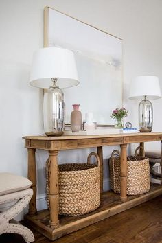 Beige x-stools flank a reclaimed wood console table fitted with a shelf holding seagrass baskets and topped with mercury glass lamps placed on either side of a light gray abstract art piece.