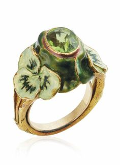 RENÉ LALIQUE - AN ART NOUVEAU PERIDOT AND ENAMEL RING, CIRCA 1900. Set with an oval-cut peridot between two raised enamel pansies, to the textured gold hoop, mounted in gold, signed Lalique.