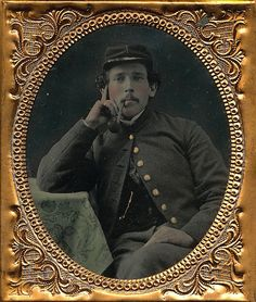 Sixth plate ambrotype of a Union soldier posing as if some deep thought. Resting with his elbow on the table at his side with a burl pipe clenched in his teeth, he wears a chasseur cap and a very plain jacket with no rank present. A great image with nice tinting on the table cloth and housed in a full leatherette case.