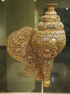 La conque (sk. sankha, tib. dundkar). Dans le bouddhisme elle représente la voix du Bouddha et son enseignement.
