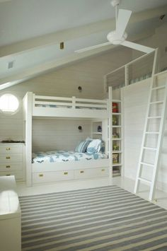 coastal bunk room.  white planked walls, pastel striped rug, built in bunk beds, and loft play space.