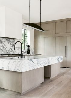 contemporary kitchen, black & white marble kitchen island, pale wood kitchen cabinets