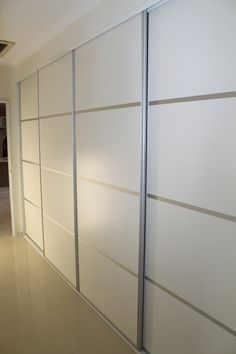 """Sliding 4 panel doors for an extra wide hallway cupboard. . The panel is white melamine in a """"sheen"""" finish with clear anodised aluminium frames. The four panel doors break up what would have been a very dull area if single panel doors had been used. The horizontal lines accentuate the width of the room creating a feeling of more space. www.formfunctionnt.com.au"""