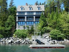 This cottage has gabled roofs, dormer windows, dual chimneys, exposed structure, stacked balconies, walls of glass overlooking the water and a private dock.