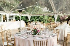 Charleston wedding reception. Clear tent, heaters, uplighting, outdoor chandelier, chiavari chairs, and floral centerpieces. Check out our blog to see more of Katy Utley's wedding at The Legare Waring House in Charleston SC. http://www.macandbevents.com