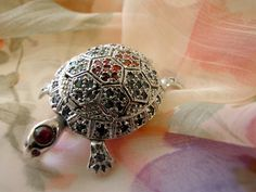 His little feet and head all move. Even his tiny tail moves. He's made of silver and has stones of emeralds, rubies and sapphires. He can be worn as a pin or a pendant.By Bunny Clarke.