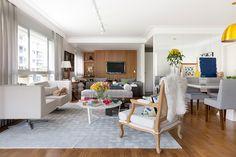Apartamento moderno, decoração da sala de estar com sofá branco, poltrona de madeira e piso de madeira.