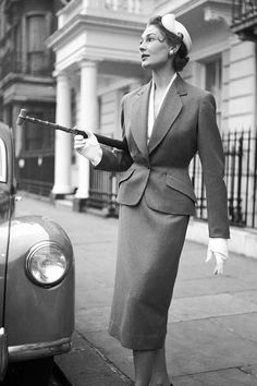 A woman modelling a tailored suit by Simon Massey, with white gloves and a cane.