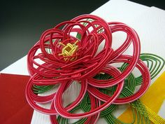 Mizuhiki is the ancient Japanese art of knotting cord into a decorative element http://www.origami-resource-center.com/mizuhiki.html