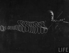 Violinist Jascha Heifetz playing in Gjon Mili's darkened studio as light attached to his bow traces the bow movement. (1952)