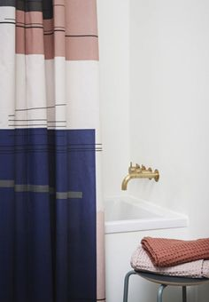 Colourful shower curtain with golden faucet. A feminine and modern touch to the bathroom.
