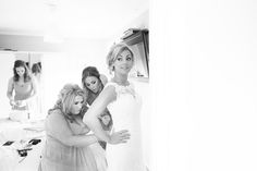 3 bride putting on dress