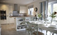 Interior designed kitchen / Dining room with a beach / seaside feel to it. Love the French Camargue Chairs in chalk white and the white wood french dining table. Reclaimed Oak effect floor. Redrow Homes 2014