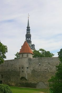 section of the Olde Towne medieval wall with one of it's many Towers, Vana Tallinn, with the spire of Raekoda seen behind the wall tower