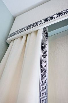 window treatments with upholstered cornice and side panels with Greek key trim…