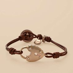 Chocolate brown leather cord bracelet with rose gold-tone heart lock charm.