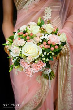 Indian Wedding Photography. Pretty in pink with a bouquet of fresh flowers complementing the pink and gold sari of the bride. Image by Kevin at Scott-Wood Photography