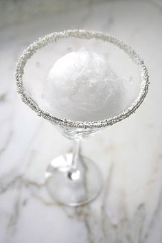 "Snowball Martini...A Martini glass, rimmed with sugar or white non-perils, ""ball"" of white cotton candy, 2 oz Whipped Cream flavored Vodka, 1 oz lemon juice. In ice-filled shaker, put in 2 oz of whipped cream vodka and 1 oz of lemon juice. Shake well. Strain over the cotton candy, ""melting"" the snowball and infusing the cocktail with sweetness."