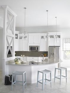 white kitchen, glass pendants, curved peninsula