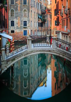 One of many foot bridges in Venice, reflecting in a small canal