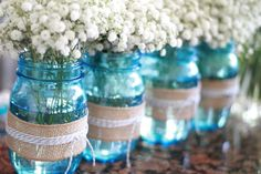 Beautiful party decor -- tinted mason jars wrapped in burlap and string with baby's breath flowers!