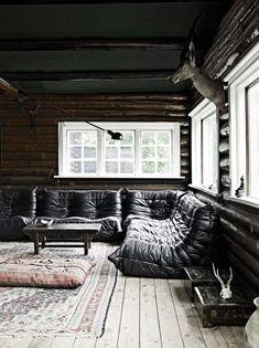 Le canapé Togo en cuir noir dans ce chalet traditionnel, dont les courbes soulignent les rondins de bois des murs