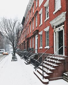 New York City in the snow, here is Greenwich Village covered in snow with a yellow cab passing down the street the brownstone with their stoops look so magical in this photo