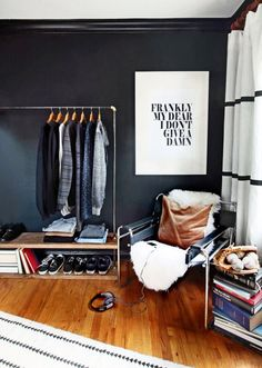 Scandinavian inspired bedroom with black walls, a rolling rack, and a modern black chair with a lamb throw