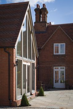 New extension to traditional farmhouse with oak and glass end wall and feature clay plain tiles to the roof