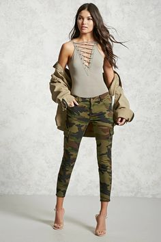 A pair of skinny jeans featuring an allover camo print, a low-rise, five-pocket construction with back snap-button flap pockets, side cargo pockets, zippered cuffs, and a zip fly front.