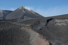 Mountain explorers look onto the volcano's active gas vent along the slopes of the volcano, Mt. Etna. The mountain's peak is in the background, showing volcanic activity and the constant discharge of steam and other gases. Sicily, Italy     http://viettelidc.com.vn