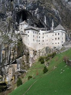 Pedjama Castle, built within the mouth of a cave.  Slovenia. so unusual but intriguing