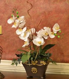 "White Silk Orchid Design in Black and Gold Bowl O147 - This stunning white silk phalaenopsis orchid is rooted by its vibrant green foliage. Small tufts of grass and miniature ivy vines cascade from a black bowl embossed with gold. This magnificent white silk orchid arrangement measures 28""H x 17""W x 10""D"
