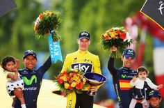2015 Tour de France winner Chris Froome of Great Britain and Team Sky celebrates  (C)alongside second placed Nairo Quintana (L) of Colombia and Movistar Team and third placed Alejandro Valverde(R) of Spain and Movistar Team .