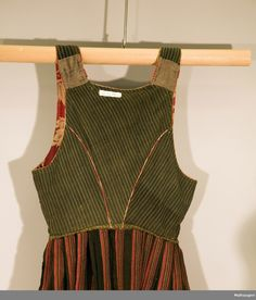 Hand-sewn evening dress with striped woolen skirt and red ullliv with major plant design. Life has the right neck behind, jointed seals and missing saddle stitched. The closure consists of four pairs of hooks and three pairs of loops for laces. Open flap. Lining of striped hand-woven wool. At the bottom of the skirt a brush strip and skoning of a grind woven tape. The skirt has a hengefald.