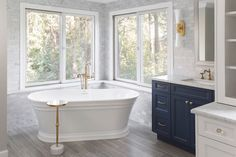 Master Bathroom Retreat - Top Knobs - Master Bathroom Retreat Natural light and a soaking tub make for a timeless retreat in this master bathroom. The cool tones of the white marble wall are softened by custom navy cabinetry and gold accents. Marble Wall, White Marble, Cool Tones, Clawfoot Bathtub, Corner Bathtub, Gold Accents, Master Bathroom, Natural Light, Navy