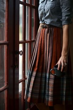 pleated plaid, Scottish style midi skirt with a leather braided belt and chambray shirt.