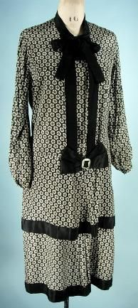 "c. 1926 Black and White Silk Print Day Black and white ""daisy"" silk print trimmed in solid black silk at tiered skirt, bow tie at neckline, stripes down front, back tie and bow at front dropped waist which has a silver embossed faux buckle."