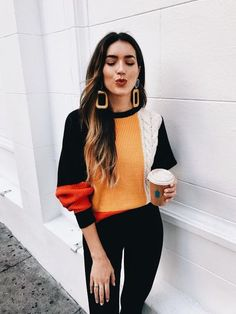 Eccentric and large earings paired with orange, white, red and black jumper.