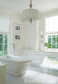 A freestanding tub takes center stage in this sunny, white bathroom. - Traditional Home ®/ Photo: John Bessler / Design: Lisa Hilderbrand with Sarah Hamlin Hastings