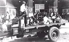 """The body of a dead Black man is displayed out in the open on a flat bed truck for other Black men to view as they were being """"Interned"""" at the convention center during the Tulsa Race Riot of 1921."""