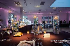 Magenta LED uplighting, pinspotting, and dance floor wash at the National Museum of American Jewish History for a wedding. Photo by Rebecca Barger Photography, lighting by Synergetic Sound + Lighting, floral decor by Carl Alan Floral Design, catering by Stephen STARR, planning by Kaleidoscope Weddings.