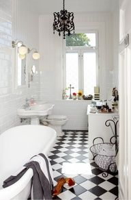 Chandelier, checkerboard floors, iron accents. classic white bathroom