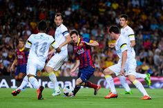 Lionel Messi of FC Barcelona duels for the ball with among players of Santos during a friendly match between FC Barcelona and Santos at Nou Camp on August 2, 2013 in Barcelona, Spain.