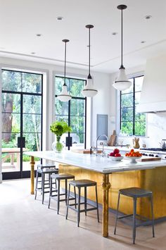 kitchen designed by William Hefner with glass doors, gray stools and yellow island with white marble countertop and metallic brass island